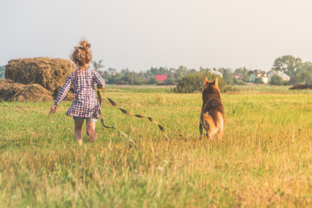 A little girl walking her dog on a sunny day. Stock fotó
