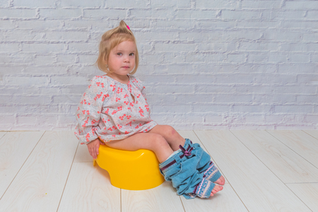 girl, baby sitting on a potty on a white brick wall background