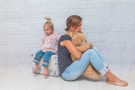 girl, mother and child on the background of a white brick wall sitting on a suitcase and a toy bear, back to each other, resentment, quarrel, parting, sadness Stock Photo