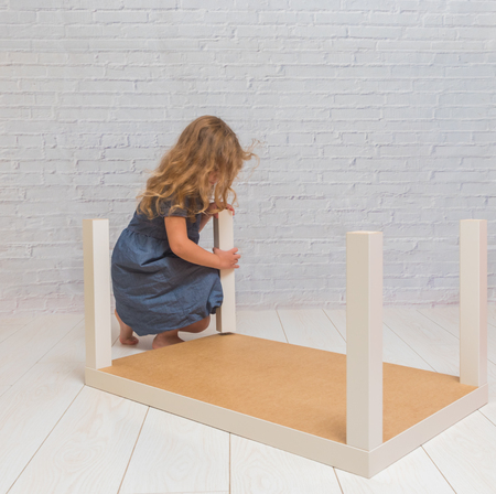 girl, child collects a new table, on backdrop of a white brick wall