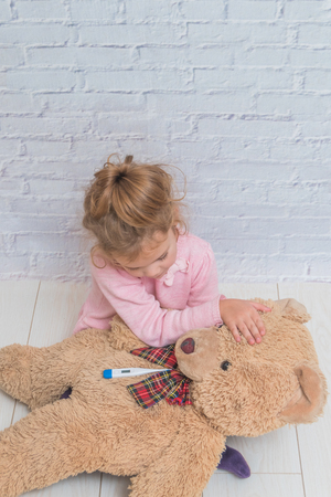 the girl, child measures the temperature of a toy bear, against a white brick wall