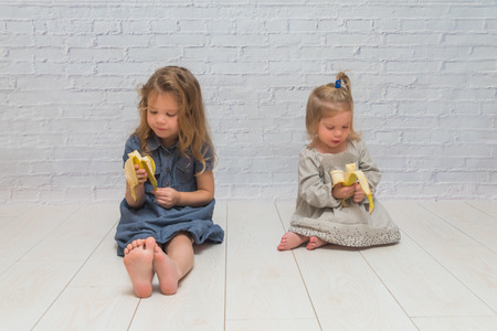 girl, a child to eat delicious healthy banana against a brick wall, healthy food