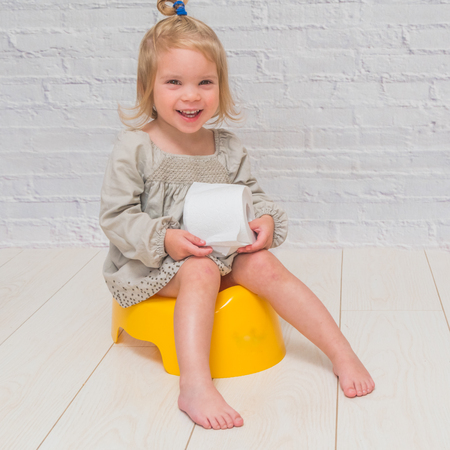 a girl in a dress, a child sitting on a yellow pot with toilet paper in his hands