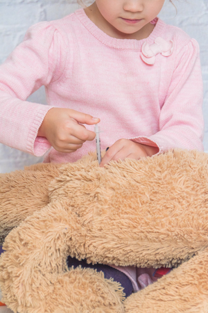 child, a girl makes a shot to the toy bear, the insulin syringe
