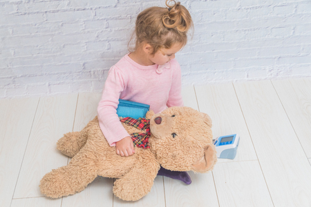 girl, a child playing doctor, measures the pressure of a bear toy Banque d'images - 110379200