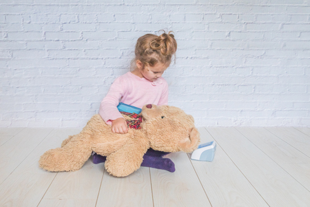 girl, a child playing doctor, measures the pressure of a bear toy Banque d'images - 110379206