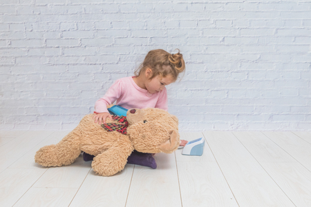 girl, a child playing doctor, measures the pressure of a bear toy Banque d'images - 110379230