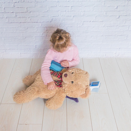 girl, a child playing doctor, measures the pressure of a bear toy Banque d'images - 110379233