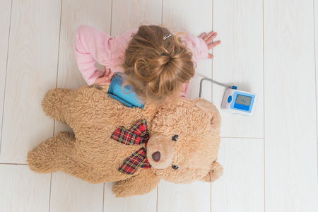 girl, a child playing doctor, measures the pressure of a bear toy 스톡 콘텐츠