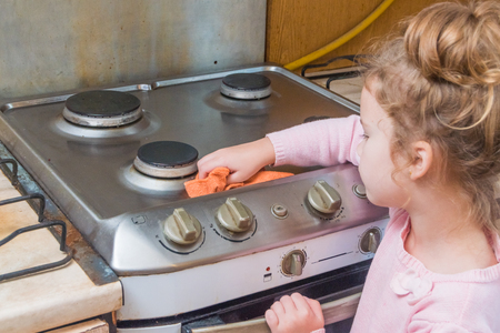 the Girl, child washes stove for cooking, in the kitchen Stock fotó