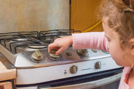 niña, un niño incluye una estufa de gas en ausencia de adultos, el riesgo de intoxicación, incendio, explosión Foto de archivo