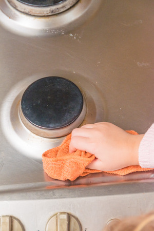 the Girl, child washes stove for cooking, in the kitchen Stock Photo