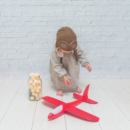 a girl, child in the helmet of the pilot with the aircraft and lights in the glass in front of a white brick wall