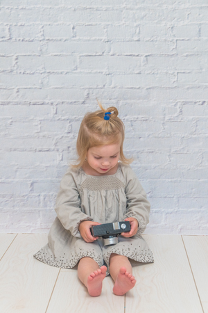 the girl, child with vintage camera on white brick wall background