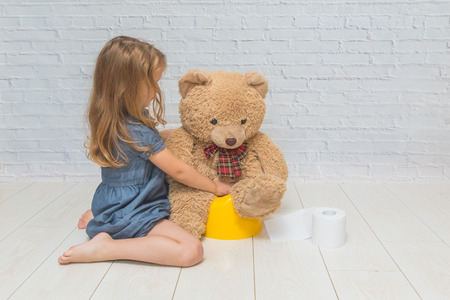 a against the background of a white brick wall, the girl sits on a potty with the child, wiping her with toilet paper