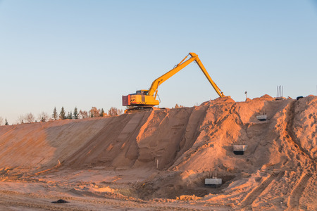 construction of the road, an excavator on a mountain of sand
