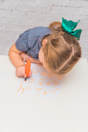 child, a girl at the table writes, draws on a piece of paper, against a white brick wall
