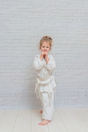 the girl, a child in a kimono on karate training works out blows and greeting