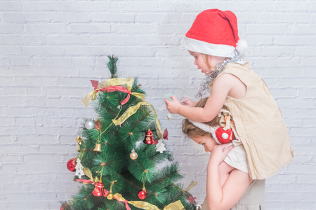 the girl, child decorates Christmas tree on white brick wall background Stock Photo
