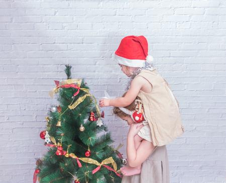 the girl, child decorates Christmas tree on white brick wall background Stock Photo