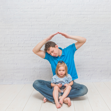 the  girl climbs, playing with dad on a white brick wall