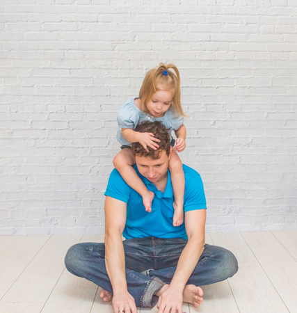 the  girl climbs, playing with dad on a white brick wall Stock Photo - 116815139
