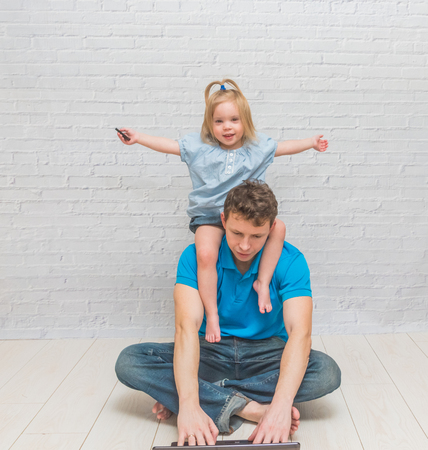 the  girl climbs, playing with dad on a white brick wall Stock Photo - 116815147