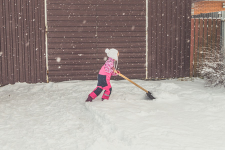 the girl, baby big shovel removes snow from the path in the backyard at the garage.