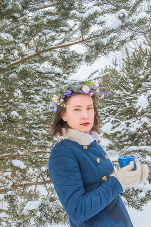 the beautiful girl stands among a Christmas tree with a mug in her hands and a wreath on her head in snowy winter