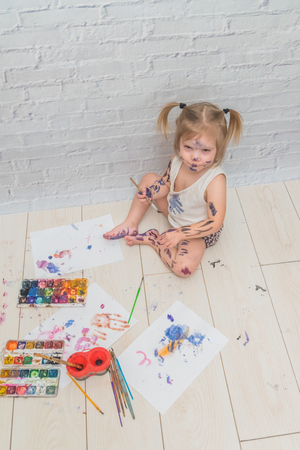 the girl, child draws with a brush and watercolor, paints, on a sheet of paper and clothing