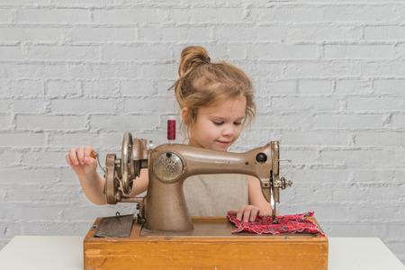 child working behind vintage sewing machine, on brick wall background