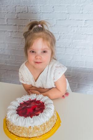 the kids eating cake on white brick wall background Stock Photo