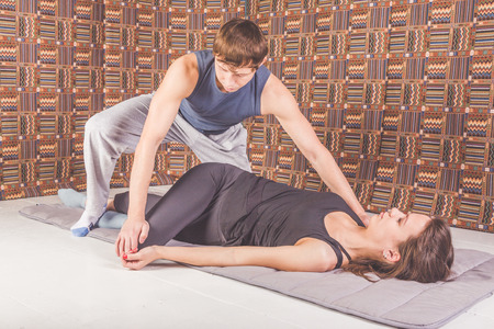 the man and woman on the floor Thai yoga massage, stretching and gymnastics, sports and health Stock Photo