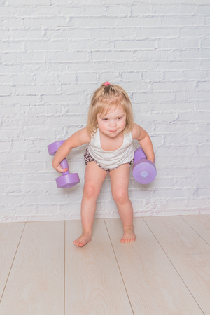 the girl, the child is engaged in fitness with dumbbells, against a white brick wall Banco de Imagens