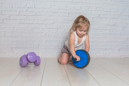 the girl, the child is engaged in fitness with dumbbells, against a white brick wall