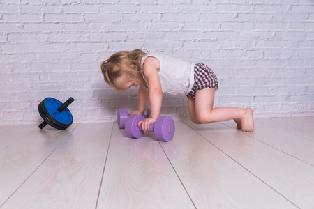 the girl, the child is engaged in fitness with dumbbells, against a white brick wall Stock Photo
