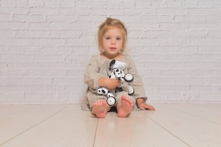 baby girl playing takes care of dog robot