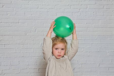 the against a white brick wall sad girl with a green balloon