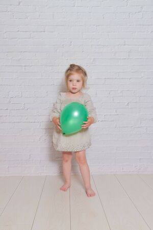 the against a white brick wall sad girl with a green balloon Stock Photo - 126768821