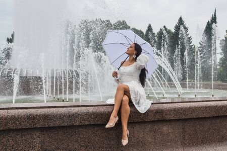 the beautiful girl in white dress and umbrella by the fountain on a cloudy day