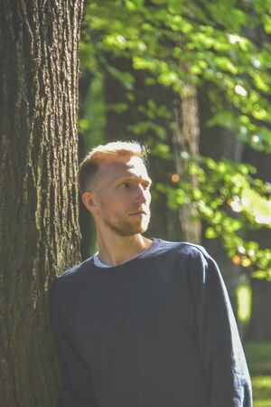 the young man with a beard in a Park among the trees