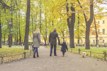 the family mom dad and daughter walking in the Park with a dog