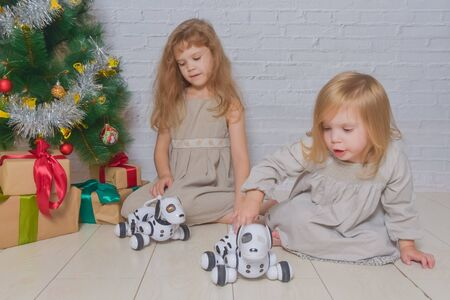 the holiday with gifts dog robot and Christmas tree two girls sisters Stock fotó - 133329701