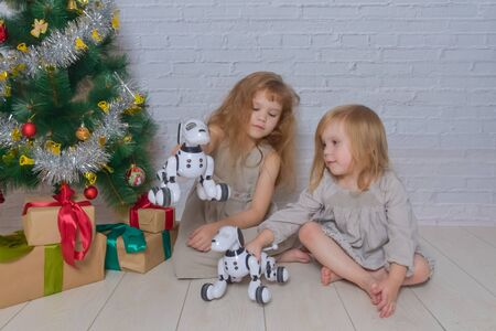 the holiday with gifts dog robot and Christmas tree two girls sisters Stockfoto