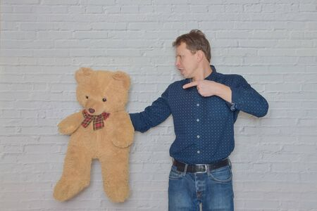 the man in a shirt gestures to the wall of white brick toy bear