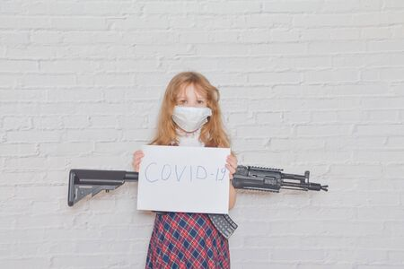 the girl with a gun and a mask on her face during the epidemic