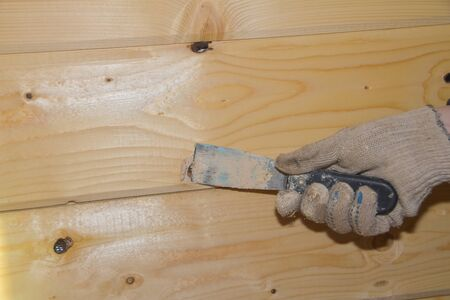 the worker puts putty on a hole in a wooden wall