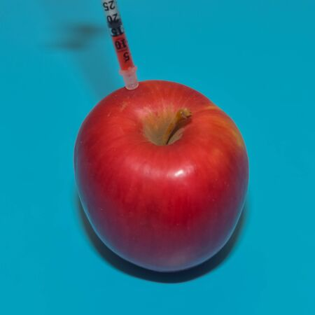 Syringe with chemicals shot in the Apple on a blue
