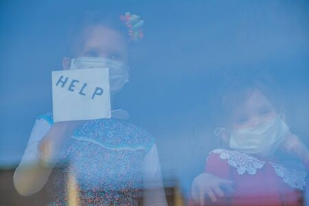 the child sits at the window in a medical mask and looks out the window