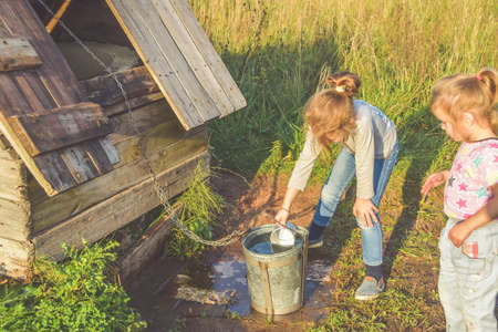 the Sunny summer day a child in a well draws water in a bucket and drinks from a metal mug
